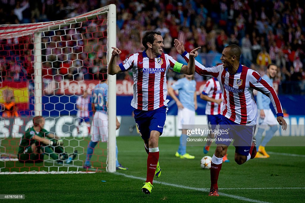 Diego Godin celebrates scoring their fourth goal with teammate Joao Miranda during the UEFA Champions League group A match between Club Atletico de...