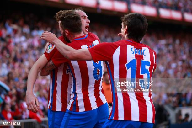 Diego Godin of Atletico de Madrid celebrates scoring their opening goal with teammates Saul Niguez and Stefan Savic during the La Liga match between...