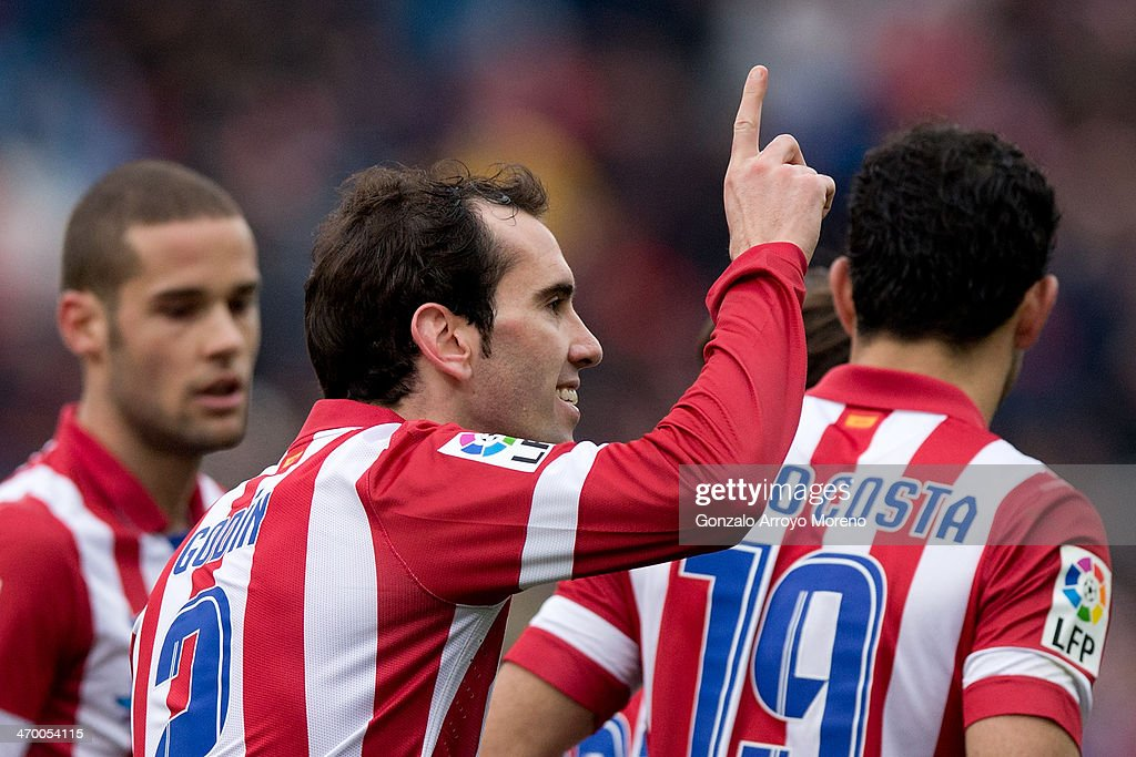 Diego Godin (2ndL) of Atletico de Madrid celebrates scoring their third goal with teammates Mario Suarez (L) and Diego Costa (R) during the La Liga match between Club Atletico de Madrid and Real Valladolid CF at Vicente Calderon Stadium on February 15, 2014 in Madrid, Spain.