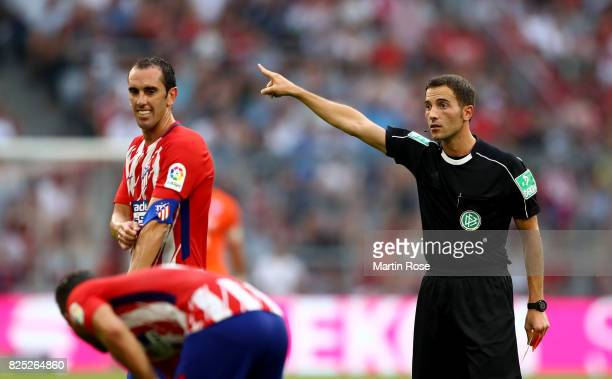 Diego Godin of Atletico Madrid is sent off of the pitch by referee Benjamin Brand during the Audi Cup 2017 match between Club Atletico de Madrid and...