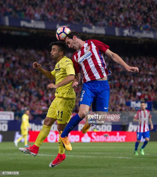 Diego Godin of Club Atletico de Madrid heads the ball while being challenged by Jaume Costa of Villarreal CF during the La Liga match between Club...