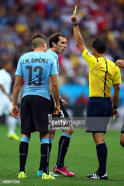 Diego Godin of Uruguay is shown a yellow card by referee Carlos Velasco Carballo during the 2014 FIFA World Cup Brazil Group D match between Uruguay...