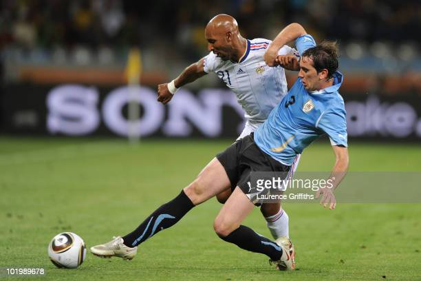 Diego Godin of Uruguay tackles Nicolas Anelka of France during the 2010 FIFA World Cup South Africa Group A match between Uruguay and France at Green...