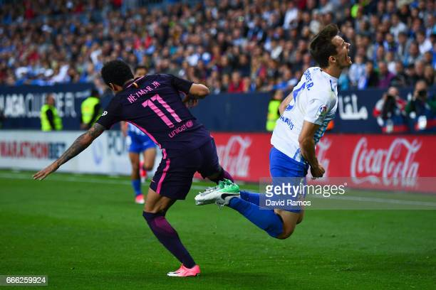 Diego Llorente of Malaga CF is brought down by Neymar Jr of FC Barcelona during the La Liga match between Malaga CF and FC Barcelona at La Rosaleda...