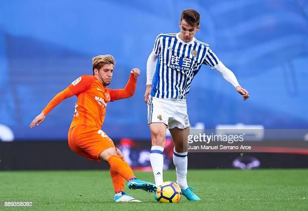 Diego Llorente of Real Sociedad duels for the ball with Sergio Gontan 'Keko' of Malaga CF during the La Liga match between Real Sociedad de Futbol...