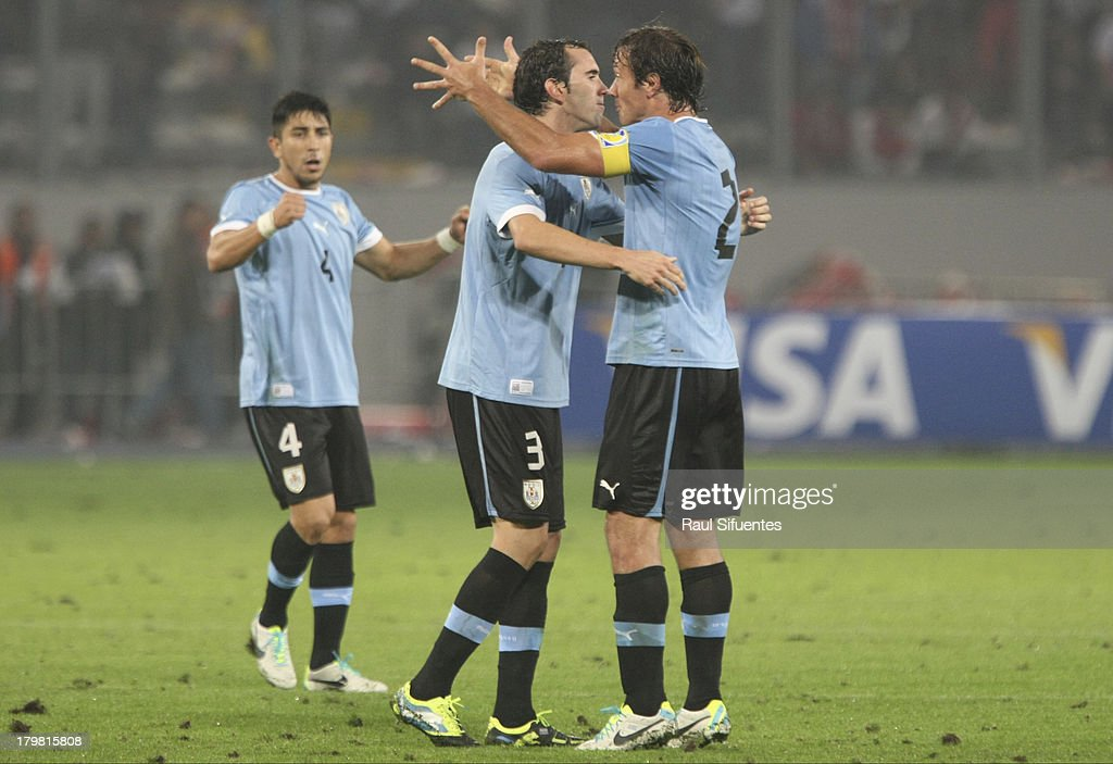 Diego Lugano and Diego Godin of Uruguay celebrates at the end of a match between Peru and Uruguay as part of the 15th round of the South American...