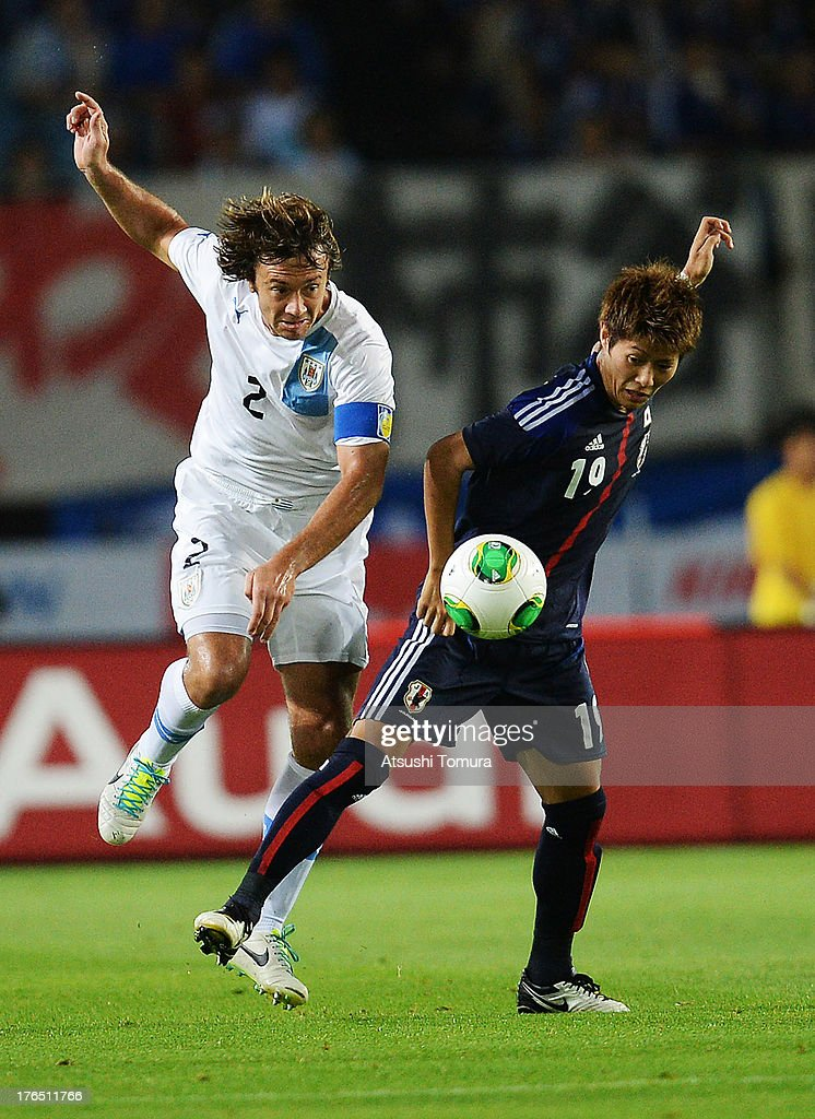 Diego Lugano of Uruguay and Yoichiro Kakitani of Japan fight for the ball during the international friendly match between Japan and Uruguay at Miyagi...