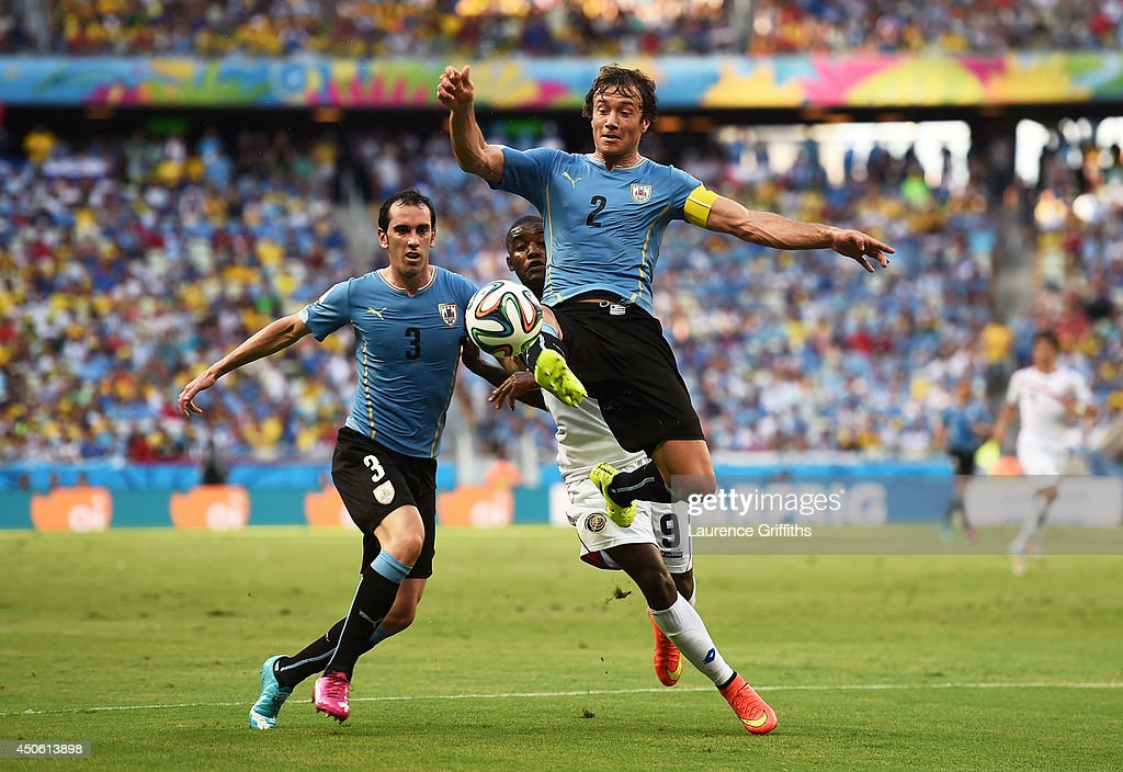 Diego Lugano of Uruguay controls the ball against Joel Campbell of Costa Rica as Diego Godin runs on during the 2014 FIFA World Cup Brazil Group D...