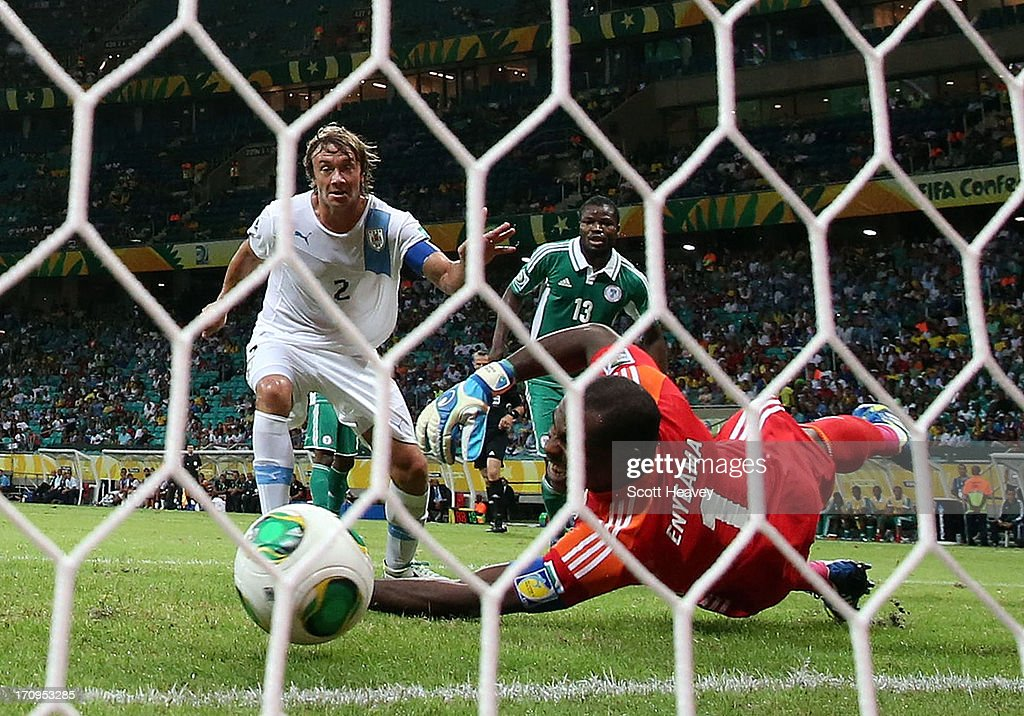 <a gi-track='captionPersonalityLinkClicked' href=/galleries/search?phrase=Diego+Lugano&family=editorial&specificpeople=274735 ng-click='$event.stopPropagation()'>Diego Lugano</a> of Uruguay scores his team's first goal past <a gi-track='captionPersonalityLinkClicked' href=/galleries/search?phrase=Vincent+Enyeama&family=editorial&specificpeople=831392 ng-click='$event.stopPropagation()'>Vincent Enyeama</a> of Nigeria during the FIFA Confederations Cup Brazil 2013 Group B match between Nigeria and Uruguay at Estadio Octavio Mangabeira (Arena Fonte Nova Salvador) on June 20, 2013 in Salvador, Brazil.