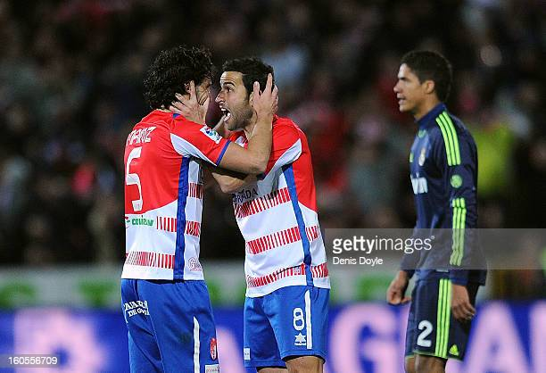 Diego Mainz and Inigo Lopez of Granada CF celebrate beside Raphael Verane of Real Madrid CF after winning 10 in the La Liga match between Granada CF...