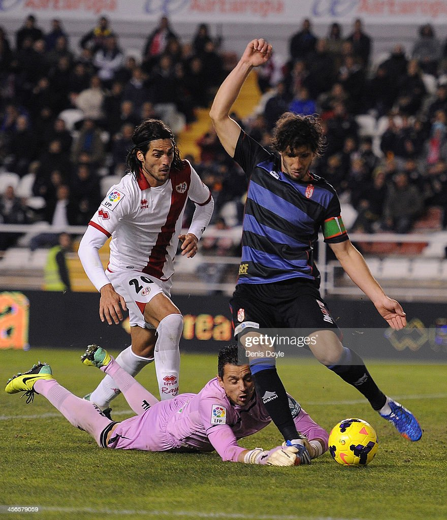 Diego Mainz Garcia #5 and goalkpeeper Roberto Fernandez of Granada CF clear the ball while being challenged by Joaquin Larrivey of Rayo Vallecano de Madrid during the La Liga match between Rayo Vallecano de Madrid and Granada CF at Teresa Rivero stadium on December 14, 2013 in Madrid, Spain.