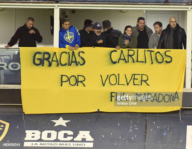 Diego Maradona displays a flag to greet Carlos Tevez during his presentation as new player of Boca Juniors at Alberto J Armando Stadium on July 13...