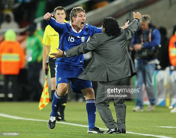 Diego Maradona head coach of Argentina celebrates with goalscorer Martin Palermo after the 2010 FIFA World Cup South Africa Group B match between...