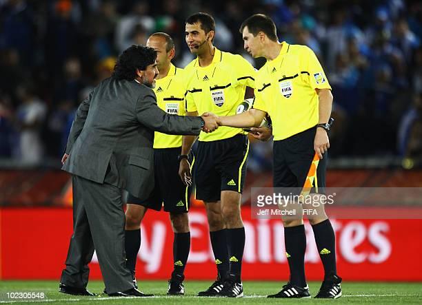 Diego Maradona head coach of Argentina shakes hands with referee Ravshan Irmatov and his assistants Rafael Ilyasov and Bakhadyr Kochkarov all of...