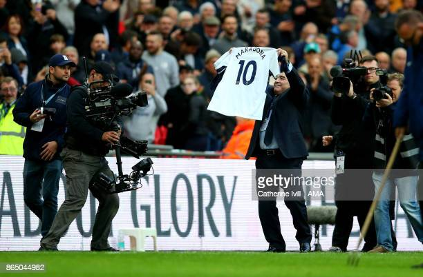 Diego Maradona holds up a Tottenham shirt with his name on during the Premier League match between Tottenham Hotspur and Liverpool at Wembley Stadium...