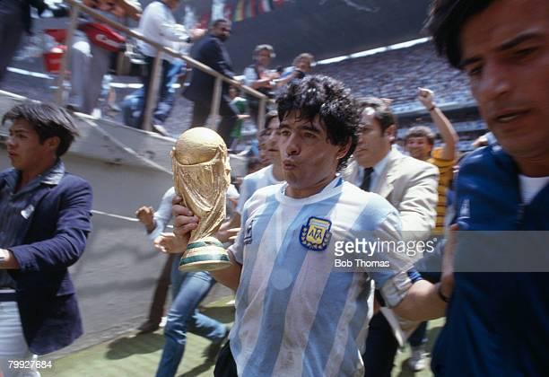 Diego Maradona leaves the field of play holding the trophy after Argentina defeated West Germany 32 in the FIFA World Cup Final played in Mexico City...