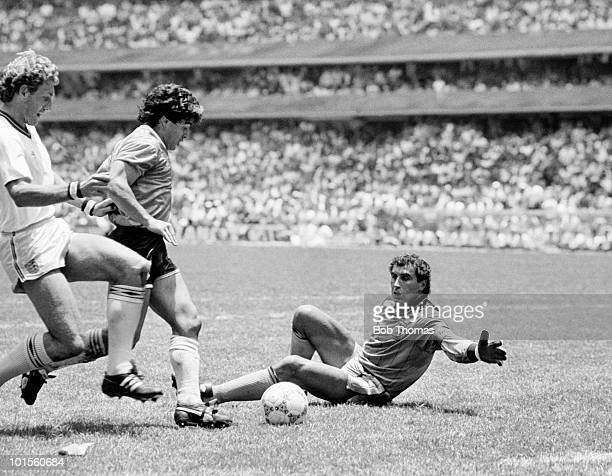 Diego Maradona of Argentina takes on Terry Butcher and goalkeeper Peter Shilton of England on his way to scoring Argentina's second goal during a...