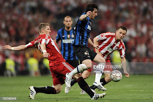 Diego Milito of Inter Milan is challenged by Bastian Schweinsteiger and Ivica Olic of Bayern Muenchen during the UEFA Champions League Final match...