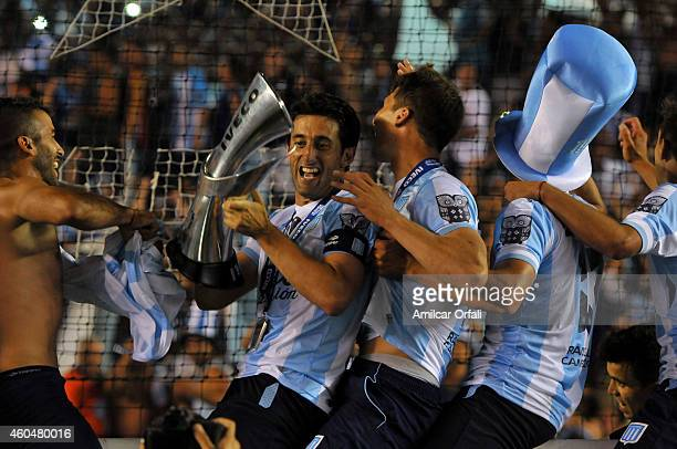 Diego Milito of Racing Club holds the trophy as he celebrates the championship after winning a match between Racing Club and Godoy Cruz as part of...