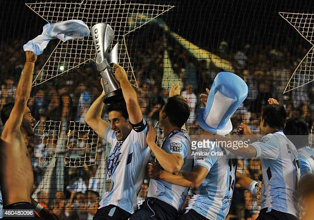 Diego Milito of Racing Club lifts the trophy and celebrates the championship after winning a match between Racing Club and Godoy Cruz as part of 19th...