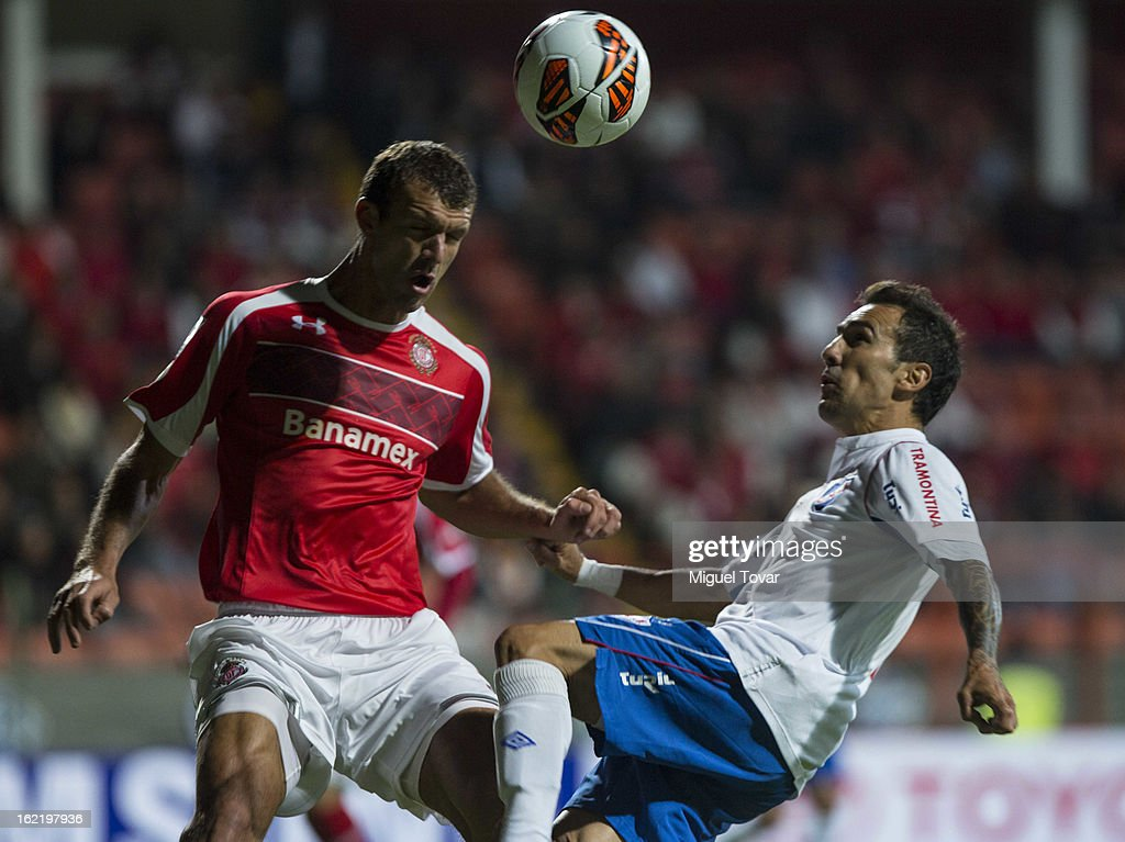 Diego Novaretti of Toluca (L) fights for the ball with <a gi-track='captionPersonalityLinkClicked' href=/galleries/search?phrase=Vicente+Sanchez&family=editorial&specificpeople=648260 ng-click='$event.stopPropagation()'>Vicente Sanchez</a> of Nacional de Uruguay (R) during a match for the Bridgestone Libertadores Cup at Nemesio Diez on February 19, 2013 in Toluca, Mexico.