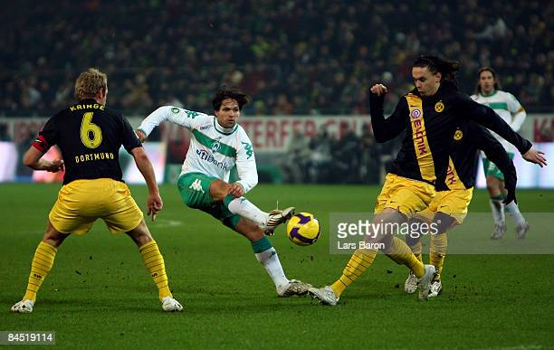 Diego of Bremen shoots on goal next to Florian Kringe and Neven Subotic of Dortmund during the round of 16 DFB Cup match between Borussia Dortmund...