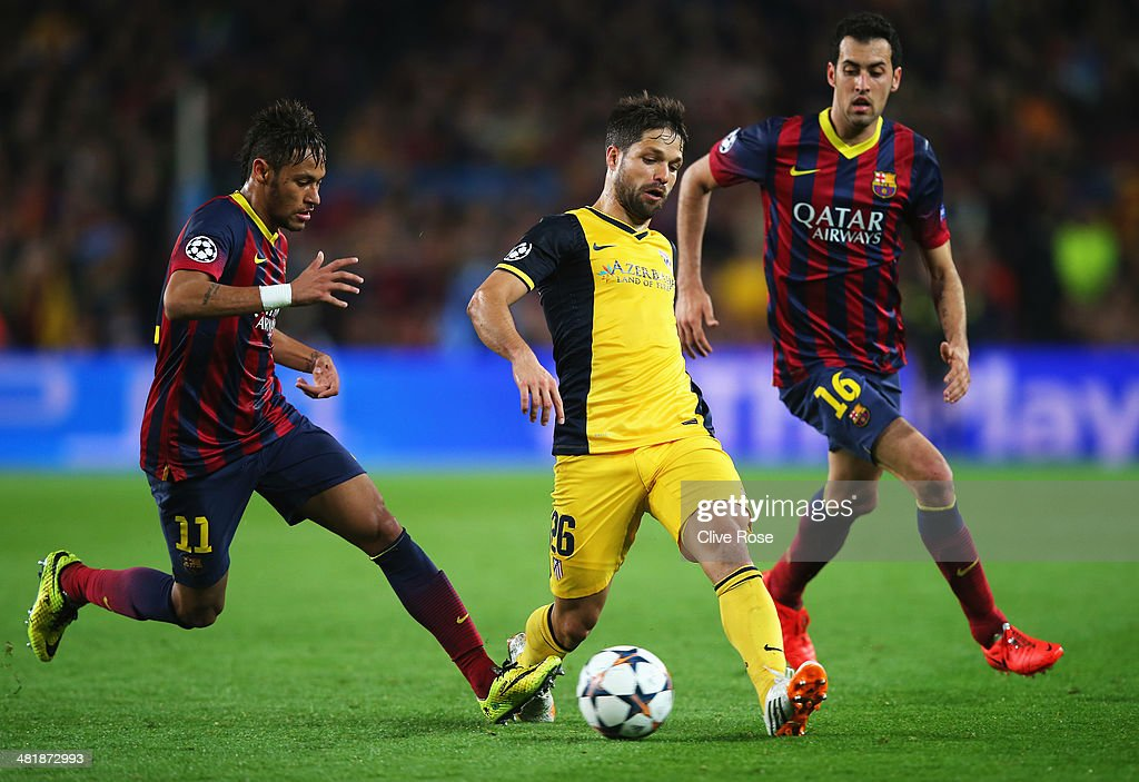 Diego of Club Atletico de Madrid is closed down by Neymar (L) and Sergio Busquets of Barcelona during the UEFA Champions League Quarter Final first leg match between FC Barcelona and Club Atletico de Madrid at Camp Nou on April 1, 2014 in Barcelona, Spain.