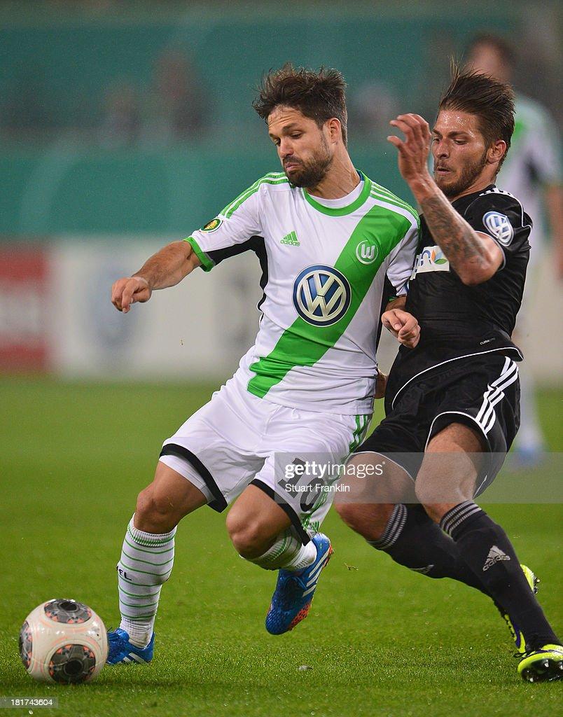 Diego of Wolfsburg is challenged by Jürgen Mössmer of Aalen during the second round DFB cup match between VfL Wolfsburg and Vfr Aalen at Volkswagen Arena on September 24, 2013 in Wolfsburg, Germany.