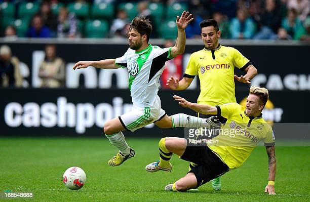 Diego of Wolfsburg is challenged by Marco Reus of Dortmund and Ilkay Guendogan of Dortmund during the Bundesliga match between Vfl Wolfsburg and...