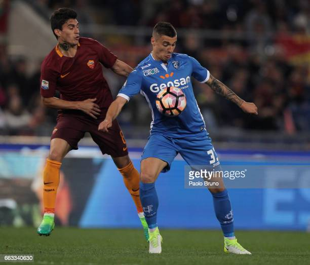 Diego Perotti of AS Roma competes for the ball with Rade Krunic of Empoli FC during the Serie A match between AS Roma and Empoli FC at Stadio...