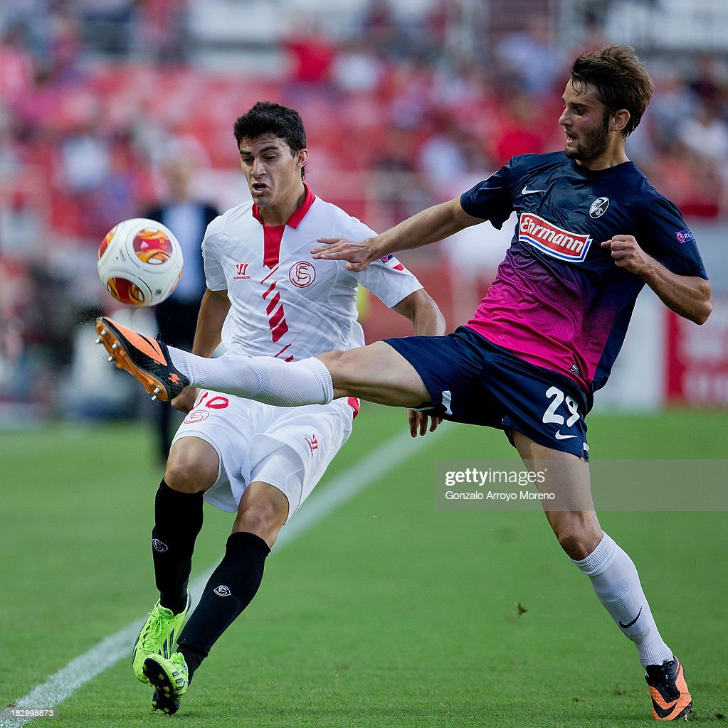 Diego Perotti of Sevilla FC competes for the ball with Tim Albutat of SC Freiburg during the UEFA Europa League group H match between Sevilla FC and SC Freiburg at Estadio Ramon Sanchez Pizjuan on October 3, 2013 in Seville, Spain.