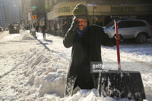 Diego Ramos who is homeless and lives under nearby building scaffolding pauses as he clears a sidewalk of snow in lower Manhattan following a snow...