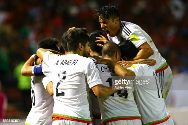 Diego Reyes of Mexico celebrates with teammates after scoring his team's first goal during the fifth round match between Trinidad Tobago and Mexico...
