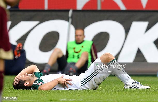 Diego Ribas da Cunha of Wolfsburg lies injured on the pitch during the Bundesliga match between VFL Wolfsburg and Hannover 96 at Volkswagen Arena on...