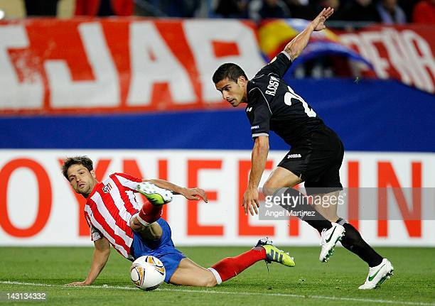 Diego Ribas of Atletico Madrid fights for the ball with Ricardo Costa of Valencia during the UEFA Europa League Semi Final first leg match between...