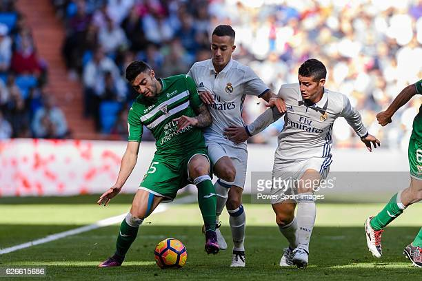 Diego Rico of Deportivo Leganes competes for the ball with Lucas Vazquez and James Rodriguez of Real Madrid during their La Liga match between Real...