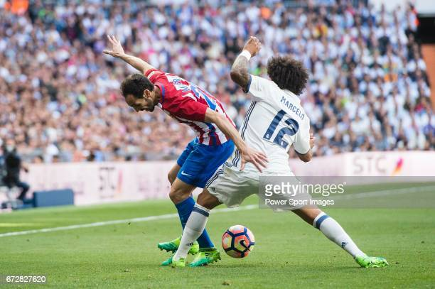 Diego Roberto Godin Leal of Atletico de Madrid battles for the ball with Marcelo Vieira Da Silva of Real Madrid during their La Liga match between...