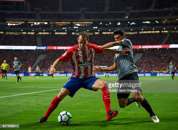 Diego Roberto Godin of Atletico Madrid competes for the ball with Chory Castro of Malaga during the La Liga match between Atletico Madrid and Malaga...