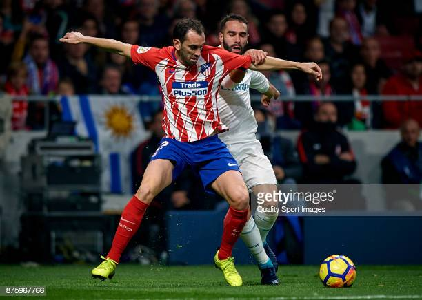 Diego Roberto Godin of Atletico Madrid competes for the ball with Daniel Carvajal of Real Madrid during the La Liga match between Atletico Madrid and...