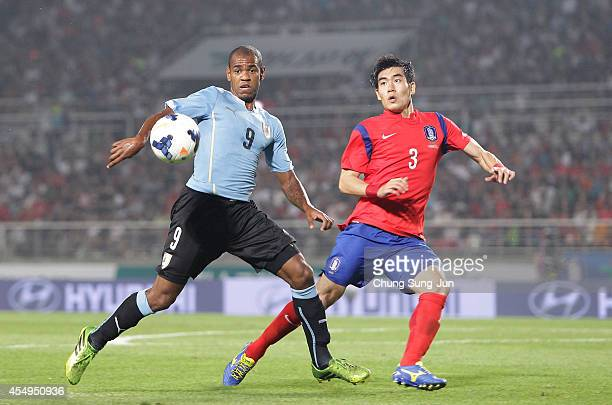 Diego Rolan of Uruguay competes for the ball with Kim JuYoung of South Korea during the international friendly match between South Korea and Uruguay...