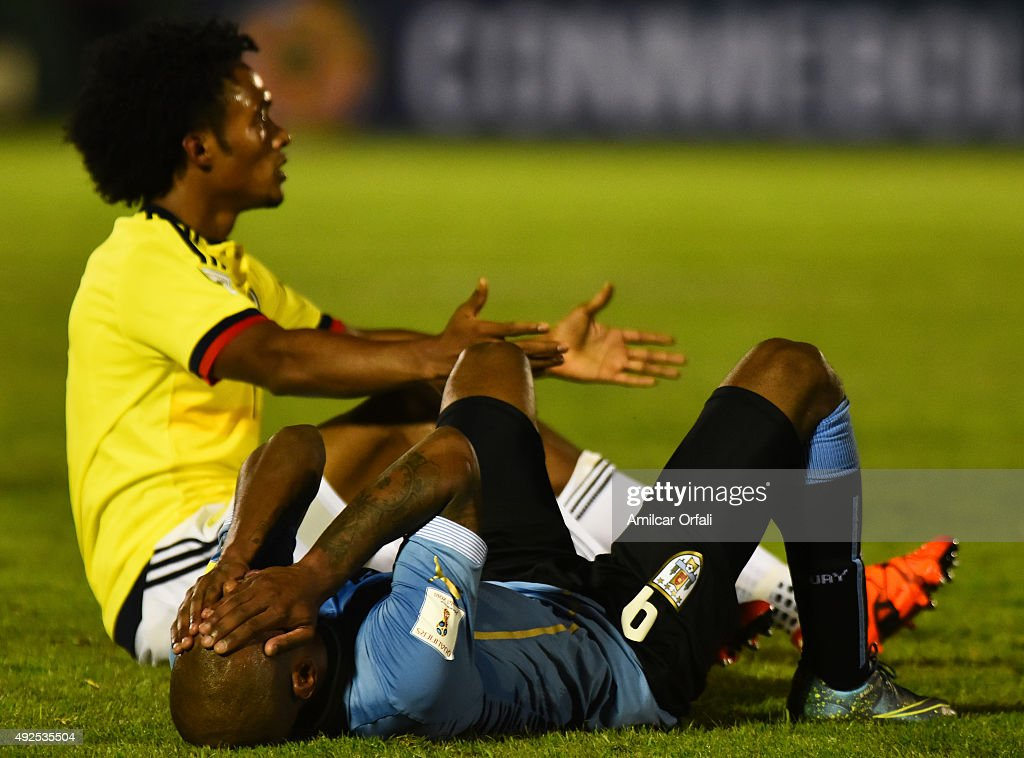 Diego Rolan of Uruguay lies injured as Juan Cuadrado of Colombia reacts during a match between Uruguay and Colombia as part of FIFA 2018 World Cup Qualifier at Centenario Stadium on October 13, 2015 in Montevideo, Uruguay.