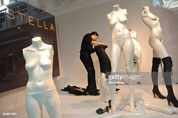 Diego Sanabria dresses a mannequin in the window of an HM store in New York Thursday November 10 2005 Within minutes the clothes of designer Stella...