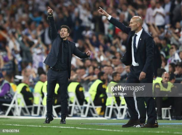 Diego Simeone manager of Atletico Madrid and Zinedine Zidane head coach of Real Madrid signal from the touchline during the UEFA Champions League...