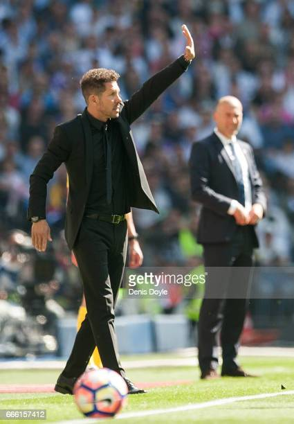 Diego Simeone of Club Atletico de Madrid reacts beside Real Madrid manager Zinedine Zidane greets Head coach before the La Liga match between Real...