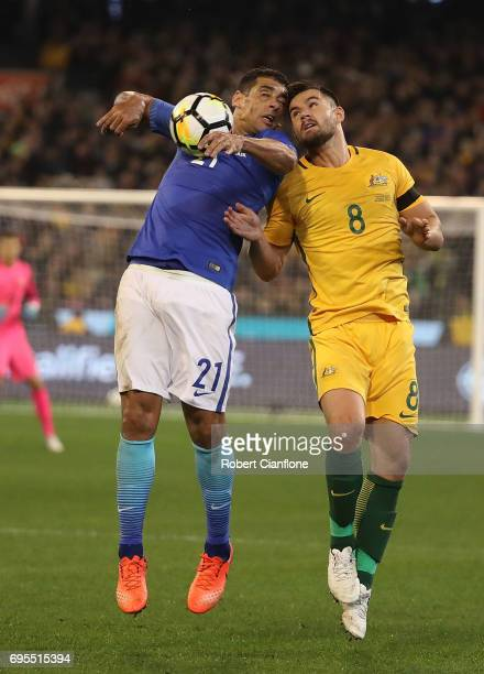 Diego Souza Andrade of Brazil and Bailey Wright of Australia compete for the ball during the Brasil Global Tour match between Australian Socceroos...