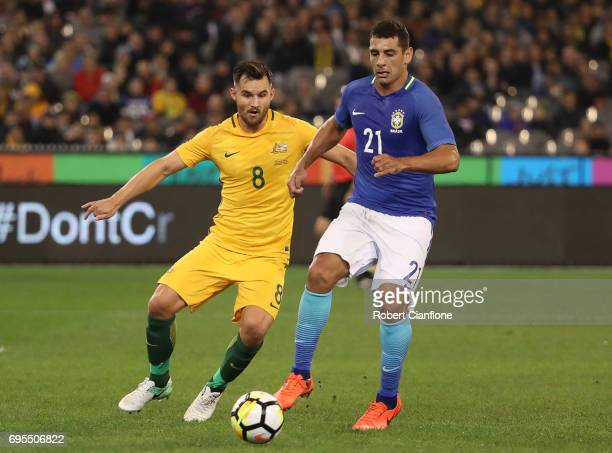 Diego Souza Andrade of Brazil is pressured by Bailey Wright of Australia during the Brasil Global Tour match between Australian Socceroos and Brazil...