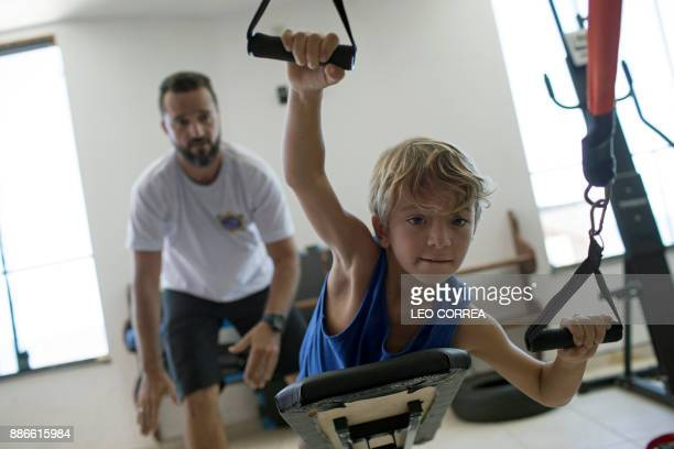 Diego Souza exercises with the assistance of his surfing teacher David Santos at the 'Inside Fit' surf training centre in Saquarema Rio de Janeiro...
