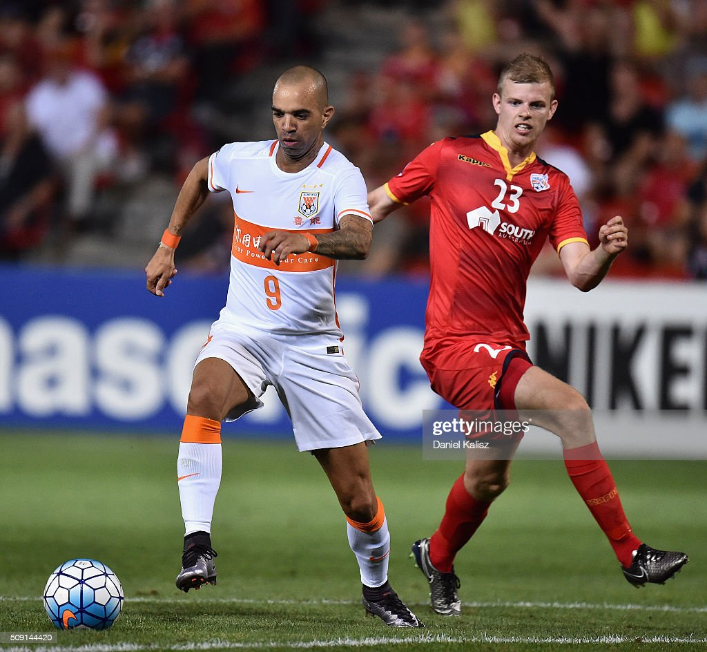 Diego Tardelli Martins of Shandong Luneng competes for the ball with Jordan Elsey of United during the AFC Champions League playoff match between Adelaide United and Shandong Luneng at Coopers Stadium on February 9, 2016 in Adelaide, Australia.