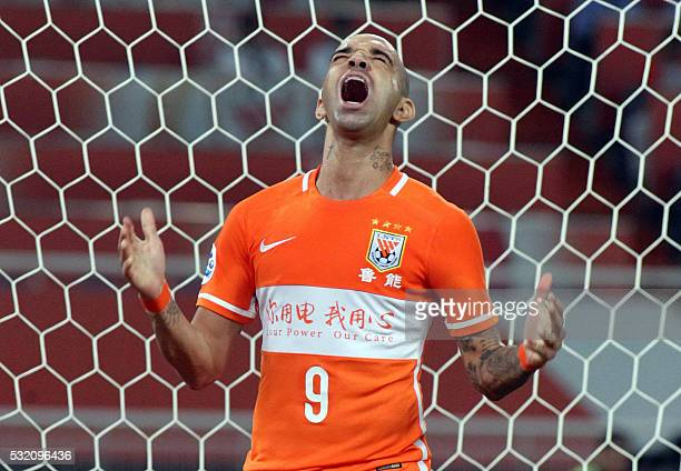 Diego Tardelli Martins of Shangdong Luneng FC reacts after missing a goal during the AFC Champions League round of 16 first leg match in Jinan in...
