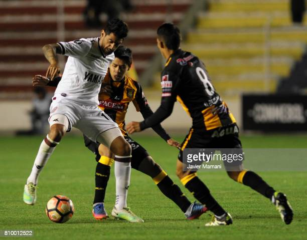 Diego Wayar and Diego Bejarano of The Strongest fight for the ball with Roman Martinez of Lanus during a first leg match between The Strongest and...